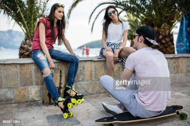 skating squad on a break - girls open legs stock photos and pictures