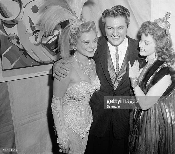 Skating star Sonja Henie welcomes pianist Liberace and actress Susan Hayward to her star spangled party at Ciro's nightclub which she took over for...