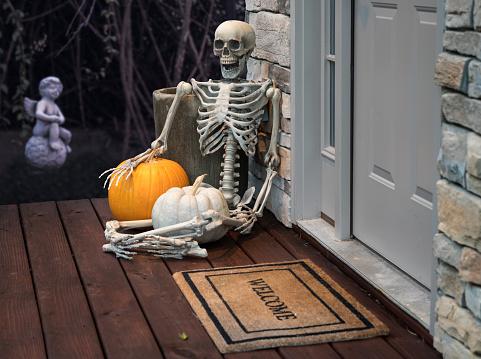 Skeleton and pumpkins in doorway for Halloween 614531096