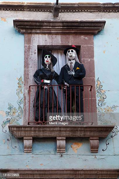 Skeleton dolls on balcony during Day of the Dead
