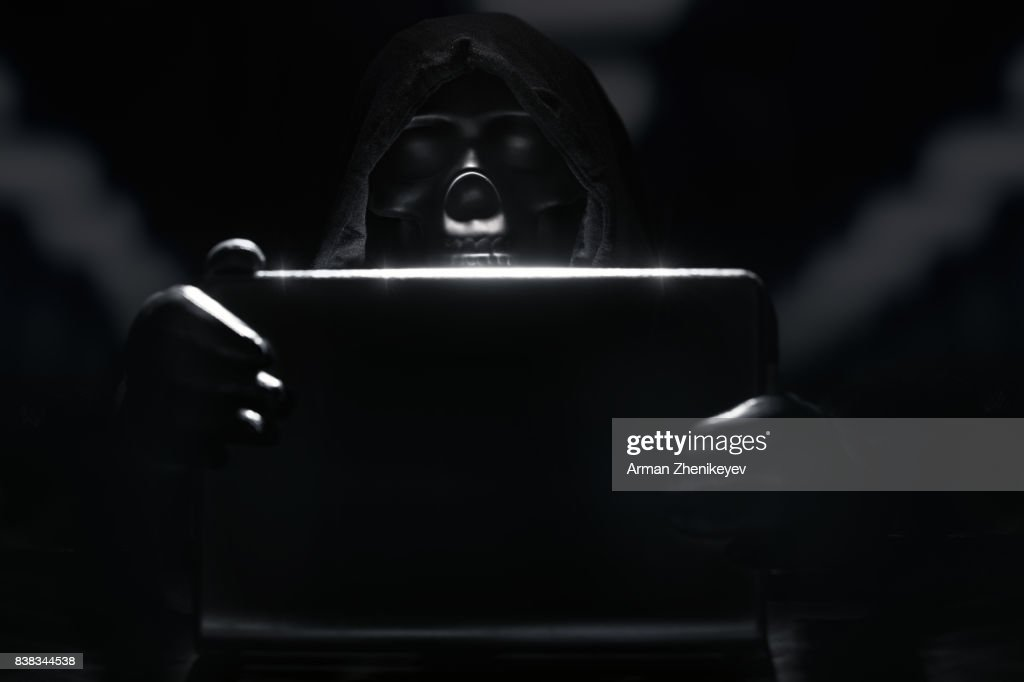 Skeleton in hood and gloves hacking computer network : Stock Photo