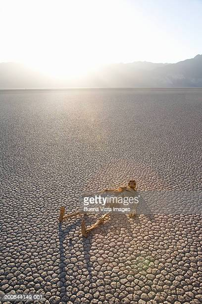 skeleton lying on cracked earth in desert - funny skeleton stock photos and pictures