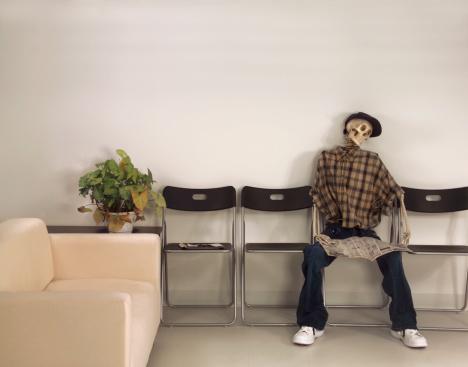 Skeleton Man Sitting Waiting Room with Newspaper 108129587