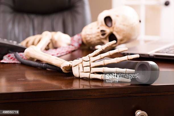 "Skeleton of man who died while waiting ""on hold"".  Telephone."