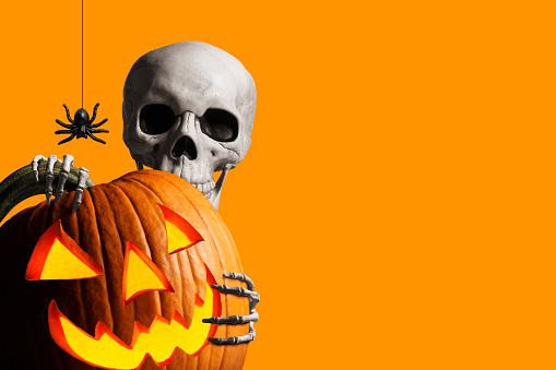 Skeleton Peeks Out From Behind A Jack O'Lantern In Front Of Orange Background 1170817332