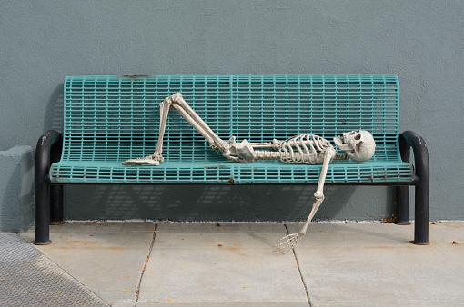 Skeleton reclining on blue bench 947062844