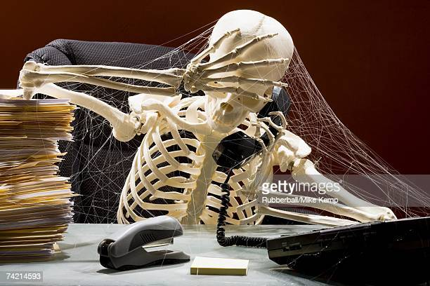 skeleton sitting at desk talking on telephone with webs and stacks of paperwork - human skeleton stock photos and pictures