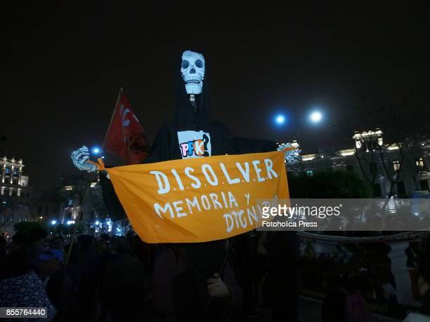 Skeleton with 'To dissolve memory and dignity' banner Hundreds of people carrying portraits of their missing relatives took to the streets of Lima in...