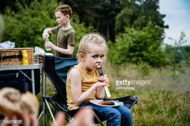 skeptical 5 year old girl eating sausage at camping cookout - sausage stock pictures, royalty-free photos & images