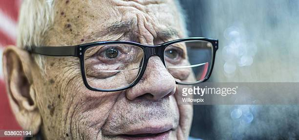 skeptical authentic real person senior adult man listening to discussion - warzen stock-fotos und bilder