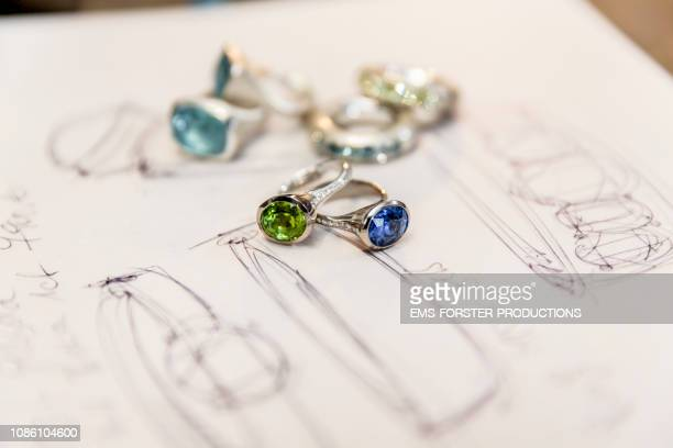 sketches and jewelry on a table - joia - fotografias e filmes do acervo