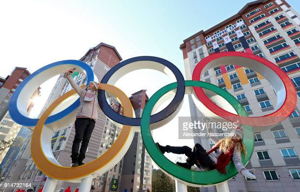 Ski coaches Kjersti Ostgaard Buaas and Chanelle Sladics of Team Slovakia pose on the Olympic Rings in the Athletes' Village during previews ahead of...