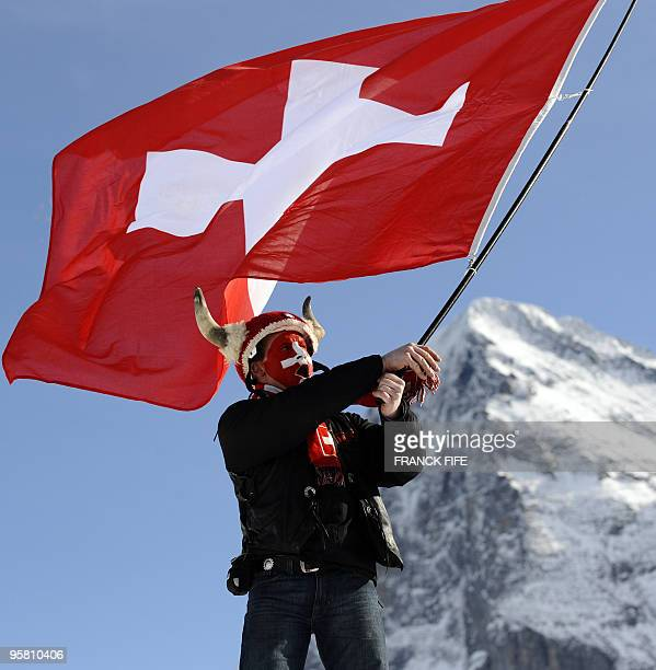 A ski fan waves a swiss flag backdropped by the Eiger mountain during the World Cup Men's Downhill event in Wengen on January 16 2010 AFP PHOTO /...