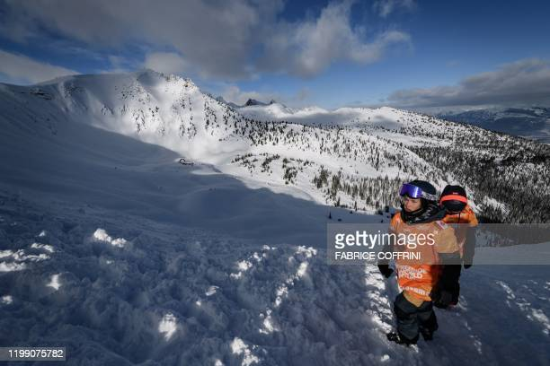 Ski freeride racer Elisabeth Gerritzen of Switzerland walks next to the competition site the Ozone face during the face check ahead of the second...