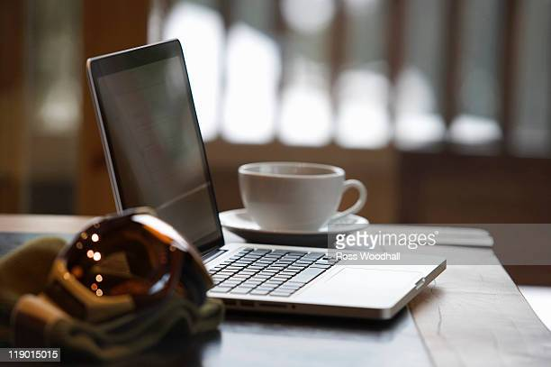 Ski goggles and laptop with coffee cup