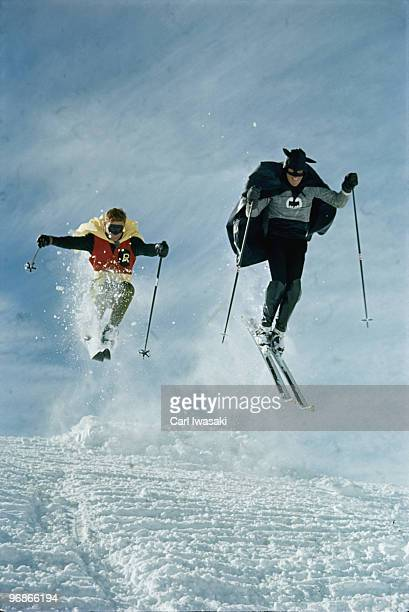 Ski instructor Roger Staub and patrol member Chuck Malloy race down slope in Batman and Robin costumes. Vail, Colorado 1966.