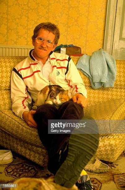 Ski Jumper Eddie Edwards of Great Britain relaxes with his cat during a feature at his home in Cheltenham England Mandatory Credit Allsport UK...