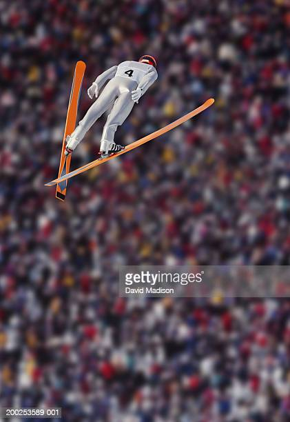 Ski jumper in air, crowd in background, rear view