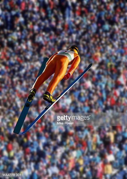 Ski jumper in mid-air jump, rear view
