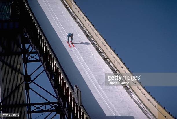 ski jumper skiing down ski jump ramp - ski jumping stock pictures, royalty-free photos & images