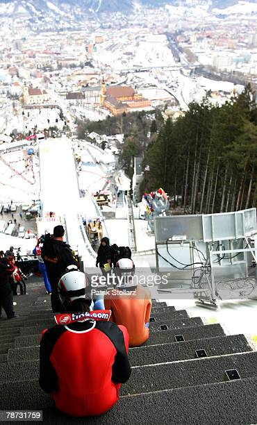 Ski jumpers sit on the steps waiting to start during the third round of the FIS Ski Jumping World Cup event at the 56th Four Hills Ski Jumping...