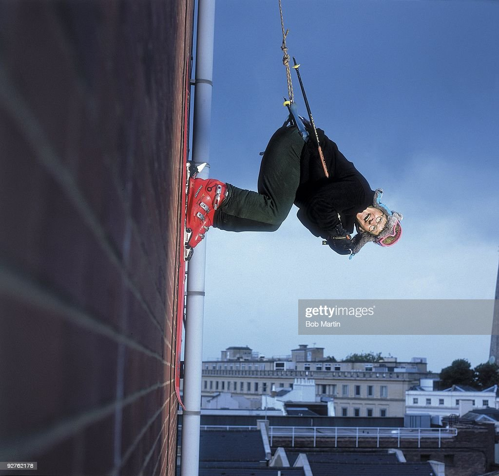 Unusual portrait of former Olympian Eddie the Eagle Edwards hanging on the side of a building while being supported by a harness and cables. Cheltenham, England 6/5/2000