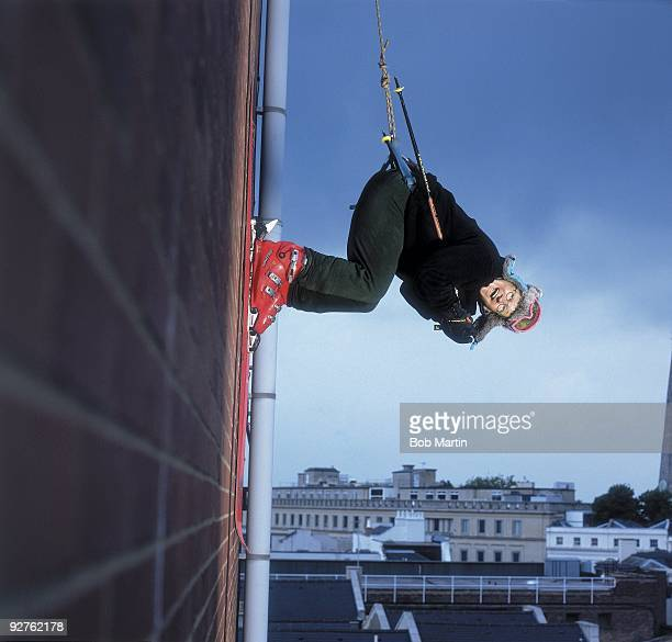 Unusual portrait of former Olympian Eddie the Eagle Edwards hanging on the side of a building while being supported by a harness and cables...