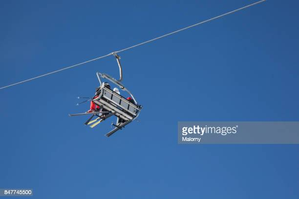 ski lift carrying people in front of clear blue sky in the alps - vorarlberg stock-fotos und bilder