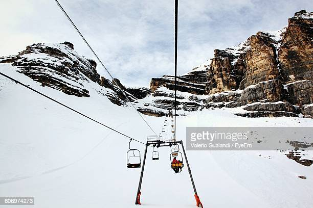 Ski Lift Over Snow Covered Field Against Sky During Winter