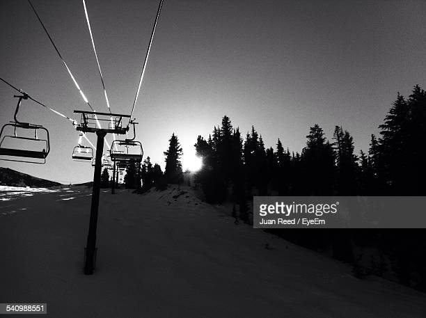 Ski Lift Over Snow Covered Mountain Against Clear Sky