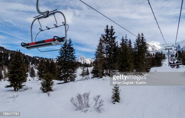 Ski Lift Over Snow Covered Mountains Against Sky
