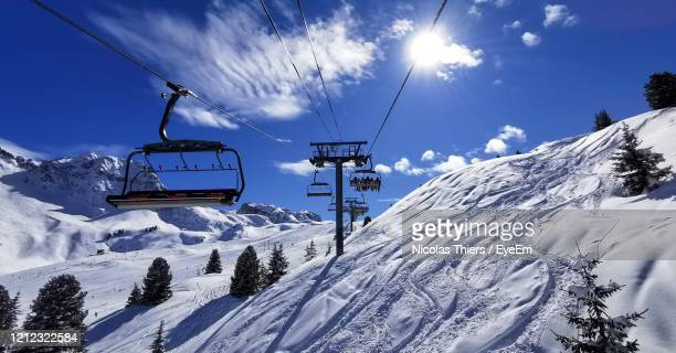 ski lift over snowcapped mountains against sky - european alps stock pictures, royalty-free photos & images