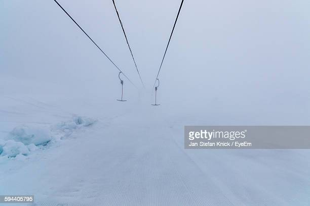 Ski Lift Over Snow-Covered Landscape In Foggy Weather