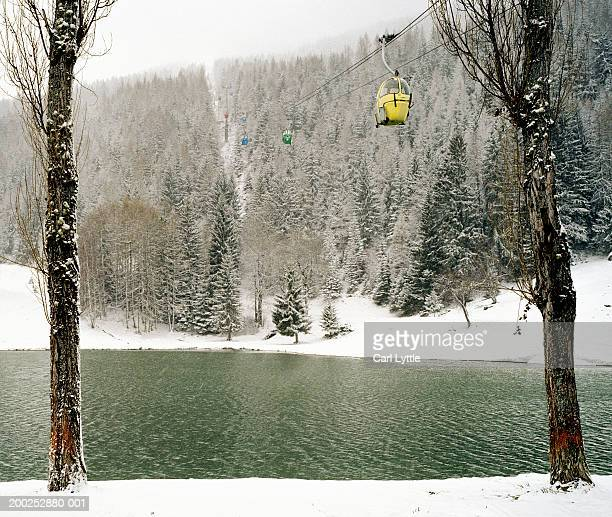 Ski lift passing over river in snowy landscape