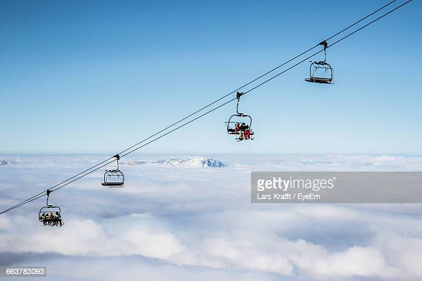 ski lifts above cloudscape against clear sky - ski lift stock pictures, royalty-free photos & images