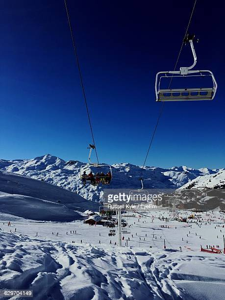 Ski Lifts Over Snow Covered Landscape Against Clear Blue Sky