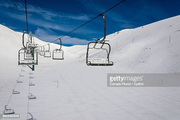 Ski Lifts Over Snow Covered Landscape Against Sky