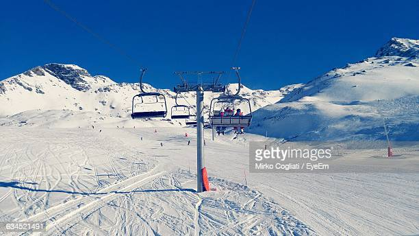 Ski Lifts Over Snowy Field Against Mountains And Sky On Sunny Day