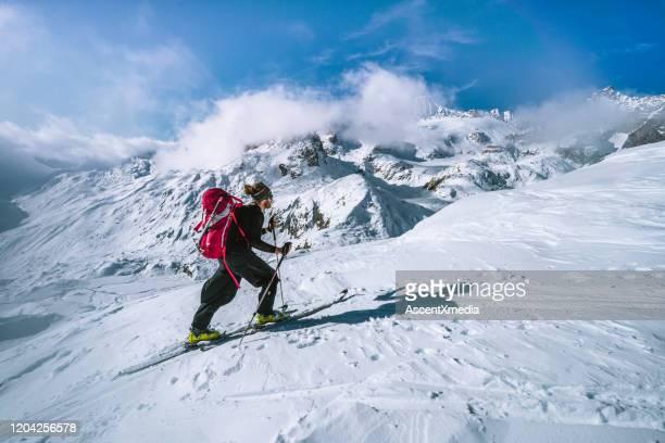 スキー登山家が雪山の尾根線を登る - 冠雪 ストックフォトと画像