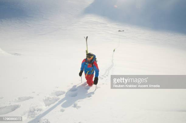 ski mountaineer climbs up steep slope to mountain summit at sunrise - three quarter length stock pictures, royalty-free photos & images