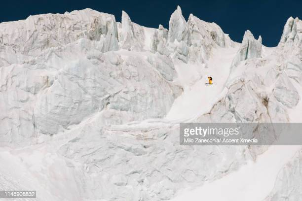 ski mountaineer descends mountain through serac field - winter sport stock pictures, royalty-free photos & images