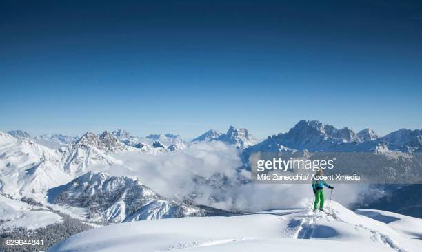 ski mountaineer pauses on mountain ridge crest - dolomites stock pictures, royalty-free photos & images