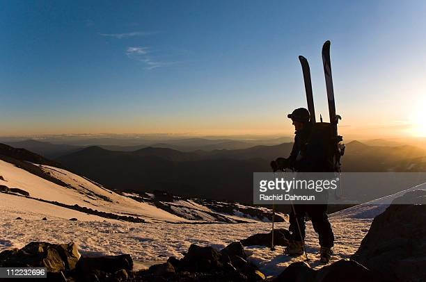 a ski mountaineer takes in the view while climbing mount shasta at sunrise, ca. - mt shasta stock pictures, royalty-free photos & images