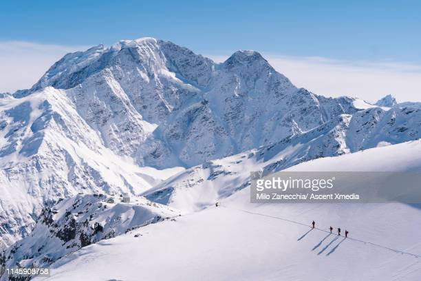 ski mountaineers advance towards mountain summit - skiing stock pictures, royalty-free photos & images