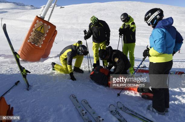 Ski Patrol emergency staff provide first aid to an injured man before evacuating him from the Val Thorens ski resort in the French Alps on January 6...