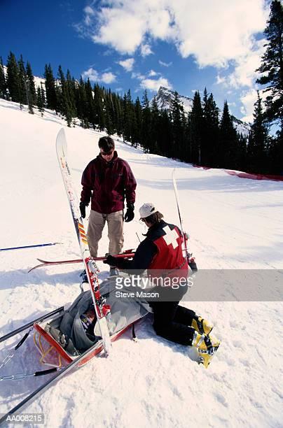 Ski Patrol Member Assisting an Injured Skier