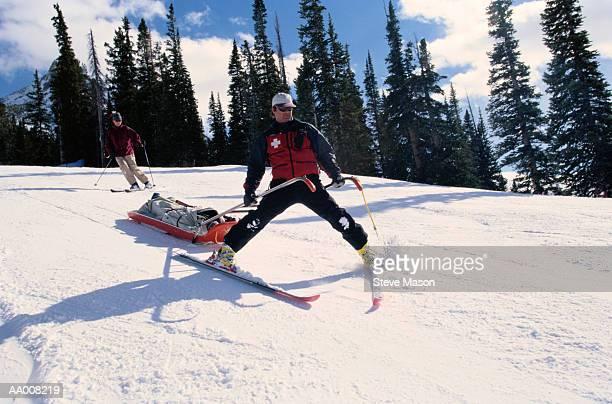 Ski Patrol Member Guiding a Stretcher Down a Hill