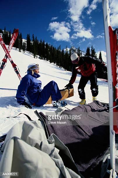 Ski Patrol Member Helping an Injured Skier