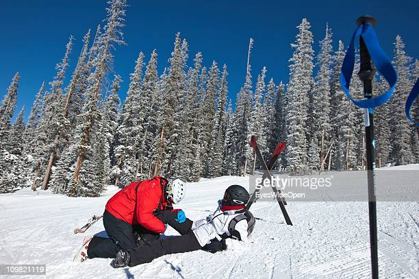 Ski Patrol on the slopes treats and checks a skier for injuries after an ski accident on February 04 2011 in Vail Colorado United States