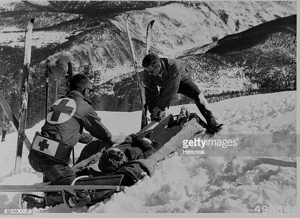 Ski patrolmen perform first aid on a ski accident victim at Winter Park Ski Area Colorado   Location Arapaho National Forest Colorado USA